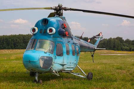 aerodrome: Blue helicopter on green grass of an aerodrome Stock Photo