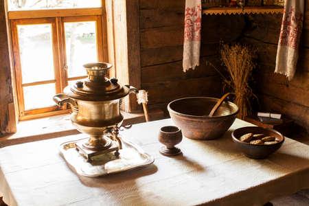 tela blanca: Todavía vida rusa con un samovar, platos de madera y una taza de madera sobre la mesa cubierta con una tela blanca