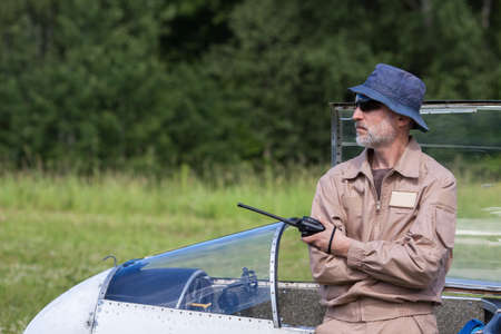 A man in a hat and sunglasses is leaning on a glider with a radio in his hand Stock Photo