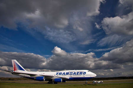 747 400: Moscow, airport Domodedovo - 27.09.2013: towing of Transaero Boeing 747-400 on the runway