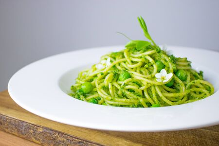Food photography of a beautiful spaghetti dish with a wild garlic pesto and peas. Stock fotó