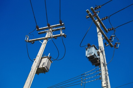 isolator high voltage: two electric poles with a transformer on a background of blue sky