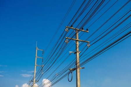 two electric poles with a transformer on a background of blue sky photo