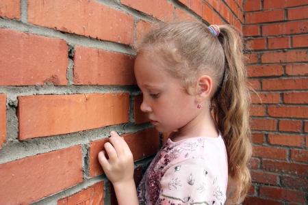 pardon: petite fille triste sur le fond d'un vieux mur de briques Banque d'images