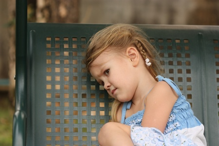 sad little child on a bench photo