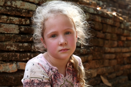 scared child: sad little girl on the background of an old brick wall