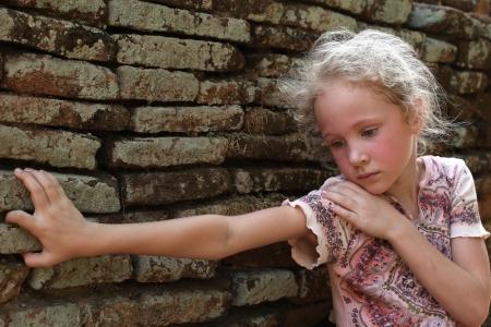 caras tristes: niña triste en el fondo de una pared de ladrillo antiguo