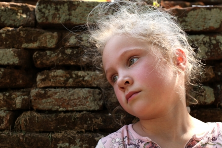 resentment: sad little girl on the background of an old brick wall