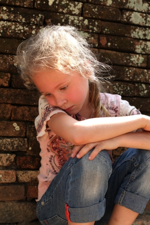 sad little girl on the background of an old brick wall photo
