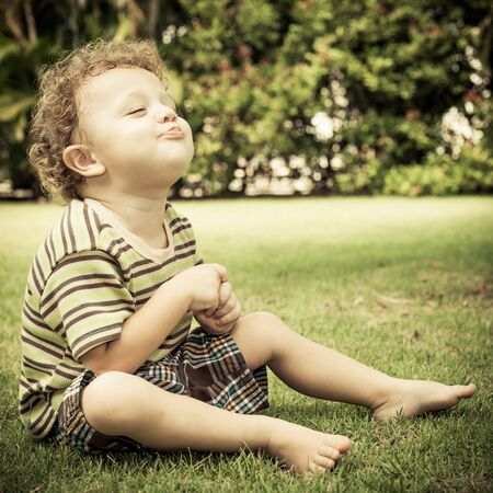 happy little boy sitting on the grass in the garden photo