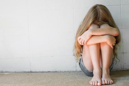 perdonar: chica triste que se sienta cerca de la pared Foto de archivo