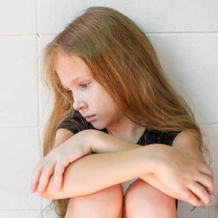 gente triste: chica triste que se sienta cerca de la pared Foto de archivo