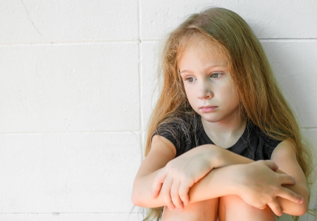 niños tristes: chica triste que se sienta cerca de la pared Foto de archivo