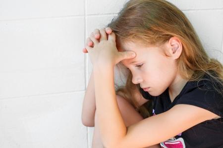 resentment: sad little girl sitting near the wall
