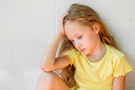 scared child: sad little girl sitting near the wall