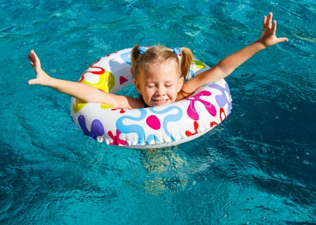 happy little girl splashing around in the pool photo