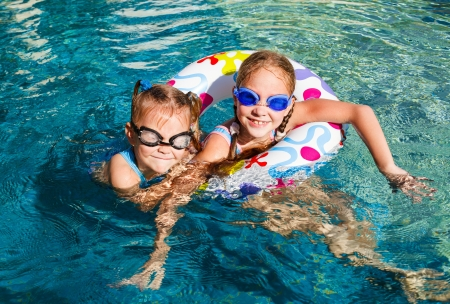 rubber ring: two happy little girls splashing around in the pool