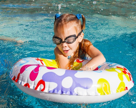 little girl in the pool  with rubber ring photo