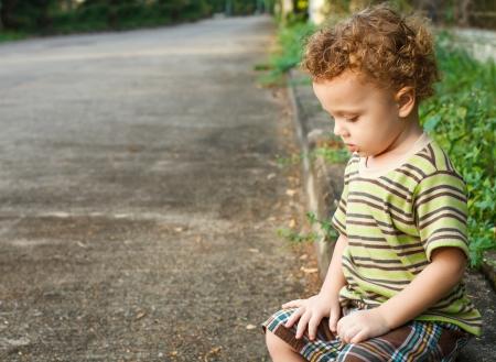 verdrietig jongetje zitten in de buurt van de weg
