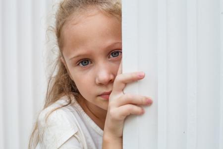 Sad little girl near the white wall. photo