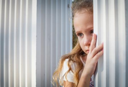 Sad little girl near the white wall. Stock Photo - 16803041