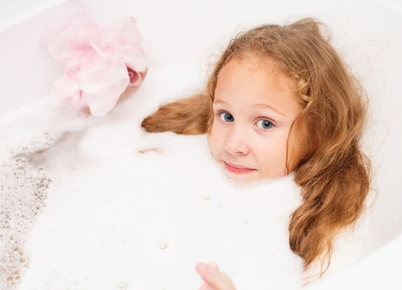 Cute eight year old girl taking a relaxing bath with foam. The symbol of purity and hygiene education. Stock Photo - 16803036