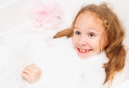 Cute eight year old girl taking a relaxing bath with foam. The symbol of purity and hygiene education. Stock Photo - 16803037