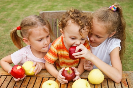 three happy children sitting at the table and eat apples photo