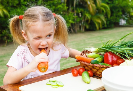 nibble: Happy little girl holding a carrots. Concept of healthy food.