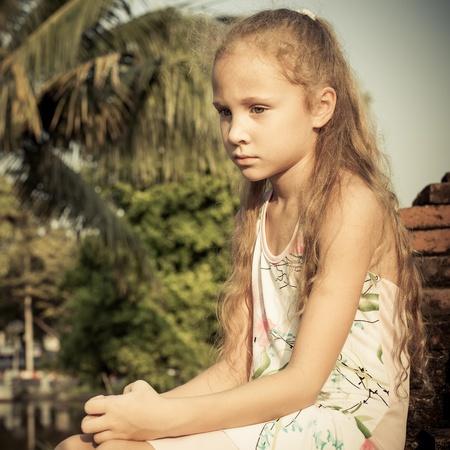 scared child: sad girl near pond on old brick wall Stock Photo