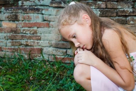 niños tristes: niña triste en el fondo de una pared de ladrillo antiguo
