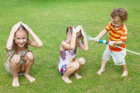 lawn sprinkler: Happy children pours a water
