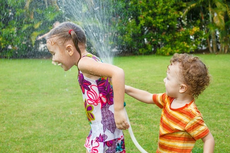 little boy is pouring a water from a hose at her sister Stock Photo - 16827210