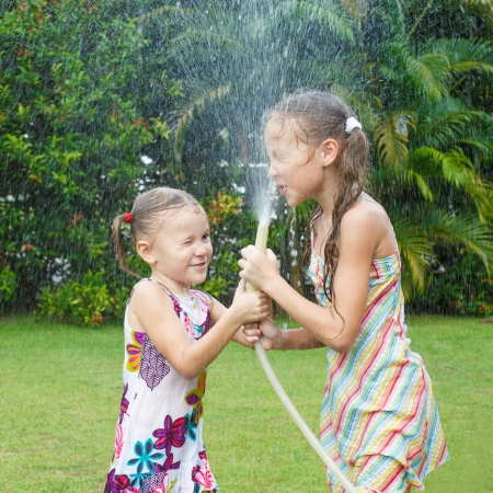 hosepipe: two little girls playing in the garden