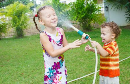 little boy is pouring a water from a hose at her sister photo