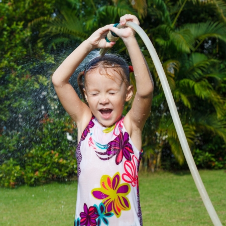 moisten: Happy little girl pours water from a hose Stock Photo