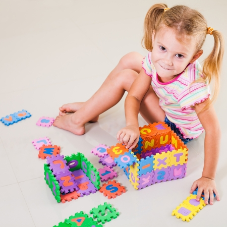 little girl sitting on the floor and building a house out of letters photo