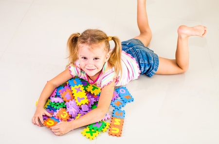 little girl lying on the floor and hugging a pile of letters photo