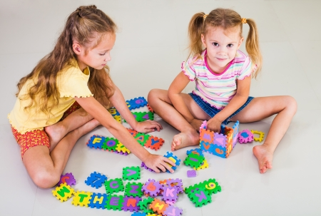 two little girls sitting on the floor and building a house out of letters photo