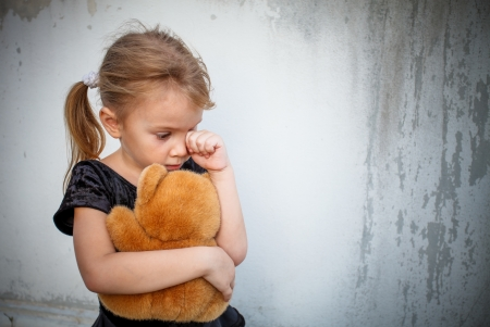 petite fille triste: petite fille triste sur fond le mur avec le jouet Banque d'images