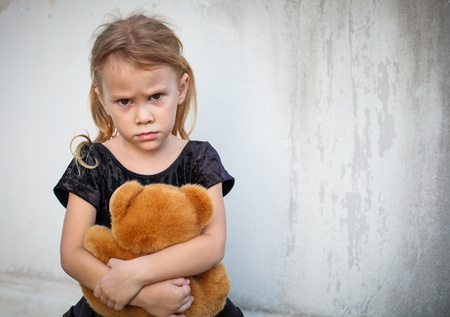 bad girl: sad little girl on background the wall with toy
