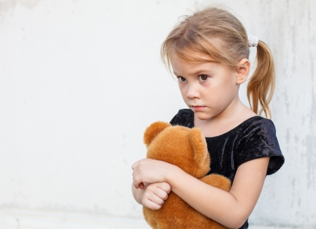 scared girl: sad little girl on background the wall with toy