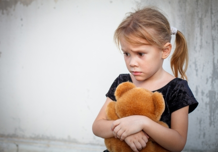 sad little girl on background the wall with toy photo