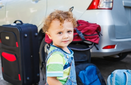 little boy standing near the car with backpacks