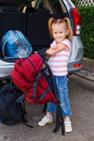little girl standing near the car with backpacks photo