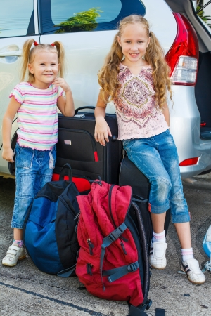 two little girls standing near the car with backpacks Stock Photo