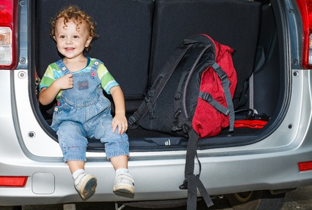 little boy sitting in the car with backpacks photo