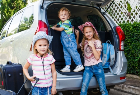 boot camp: two little girls  and boy standing near the car with backpacks Stock Photo