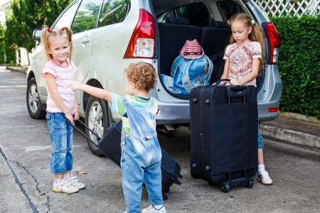 two little girls  and boy standing near the car with backpacks photo