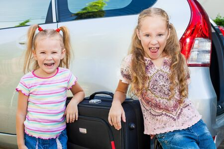 two little girls standing near the car with backpacks photo